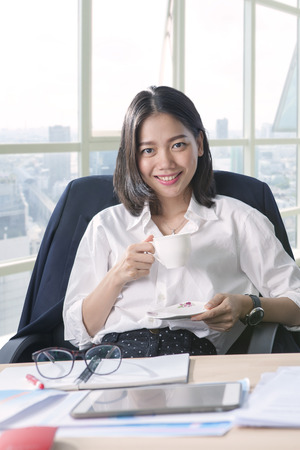 office life: working woman and beverage cup in hand toothy smiling face with happiness emotion use for people and office life Stock Photo
