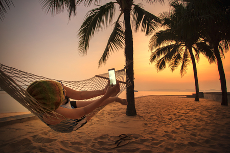 beach sunset: woman lying in beach cradle and taking a photograph by smart phone Stock Photo