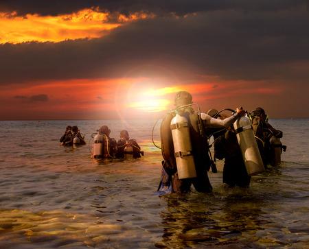 picada: grupo de buceo que se prepara para el buceo nocturno en el lado del mar contra la hermosa puesta de sol cielo Foto de archivo