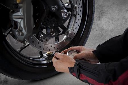 Essai de pression d'air manuel homme du pneu moto avant de voyager voyage pour véhicule de sécurité à cheval Banque d'images - 54797912