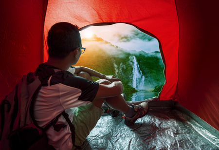 destination scenic: camping man in camper tent looking to beautiful natural water falls scenic use for people vacation traveling to destination