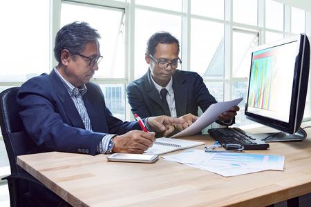 trabajando duro: Compañero del hombre mayor de trabajo de ingeniería seria reunión sobre el proyecto de discutir disparo solución sobre la mesa en la oficina sala de reuniones