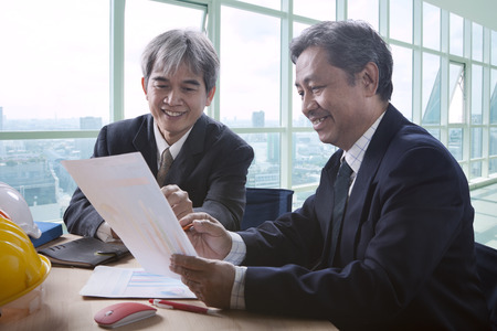 asian business man: partner of senior engineering working man serious meeting about project discussing solution shot on table in office meeting room