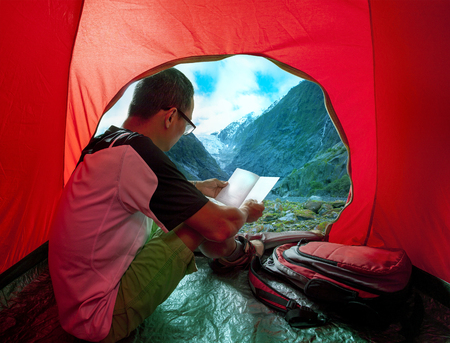 night life: camping man reading traveling guide book in camp tent against beautiful scenic of glacier mountain