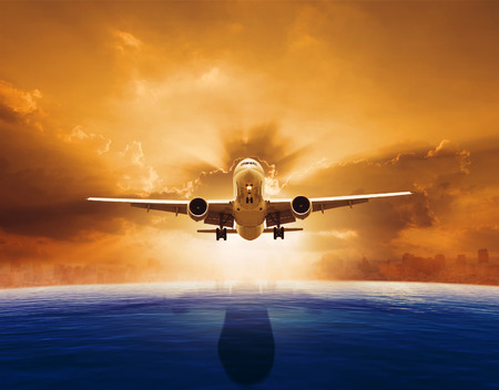 aircraft take off: passenger jet plane flying over beautiful sea level with sun set sky above and urban skyline behind