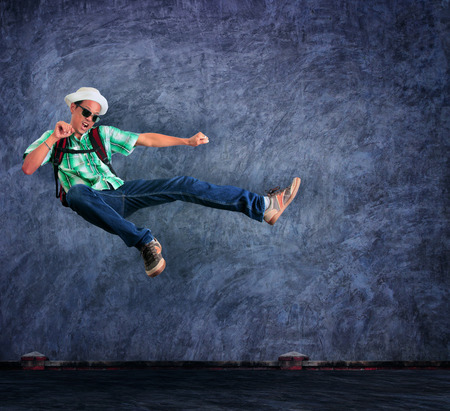 mid air: traveling man jumping mid air with exciting emotion against cement wall