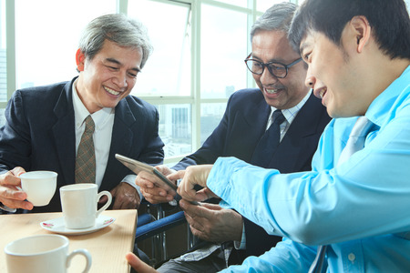 younger: relaxing emotion of business man in coffee break time with younger and senior working friend relation Stock Photo