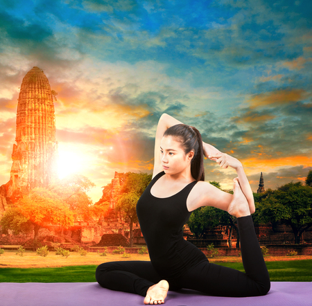 ancient yoga: asian woman health care yoga posting with asian ancient pagoda temple and sun set sky