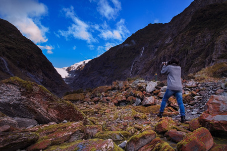 younger: younger female photographer take a photograph in franz josef glacier important traveling destination in south island new zealand Stock Photo