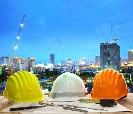 하드 모자 계획 및 아름 다운 조명 및 도시 건물에 대 한 쓰기 도구를 사용 하여 작업 테이블 작업 사이트 토지 및 도시 개발 backgound