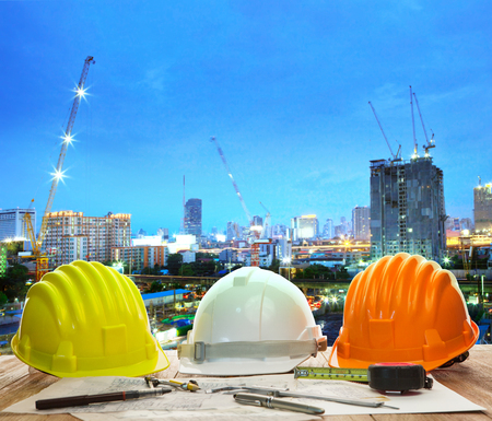 safety at work: engineer working table with hard hat plan and writing tool against beautiful lighting and urban building construction site use for land and city development backgound Stock Photo