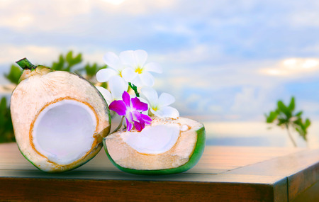 twon half of green coconut water on top  wood table with tropical orchid flowers and white  frangipani bouquet decorated