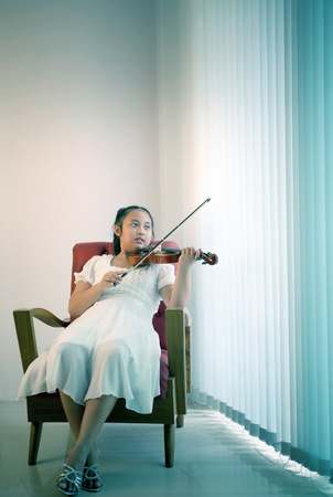 asian girl lying on sofa in living room practice to playing violin with happiness emotion photo