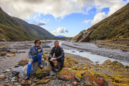 franz: couples of asian traveler taking a photograph in franz josef glacier important traveling destination in south island new zealand Stock Photo