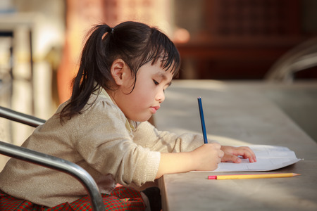 school work: asian children with yellow pencil in hand doing school home work with happiness emotion