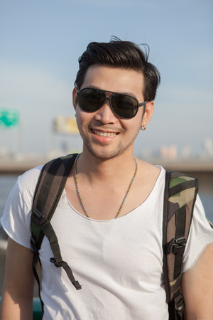 younger: close up face of younger asian man wearing sun glasses standing outdoor