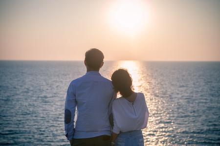 fotografía de estilo inconformista de vacaciones más joven amor pareja se relaja con la puesta de sol cielo en el destino de mar felicidad lado de la emoción