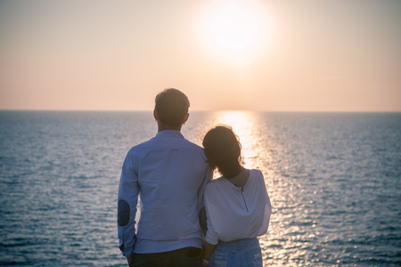 hipster photography style of younger love couples vacation relaxing with sun set sky at destination sea side happiness emotion