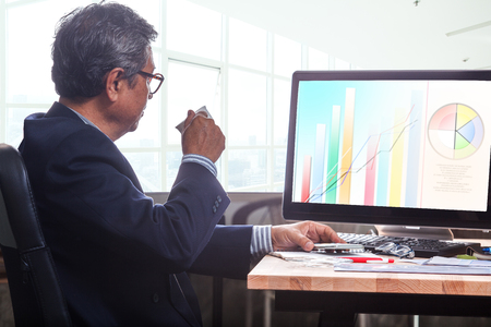 vp: senior business man working on office table with computer and business graph report , Stock Photo