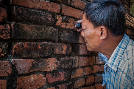 archaeologist: old Archaeologist using magnifying  lens watching on ancient old brick wall in working site