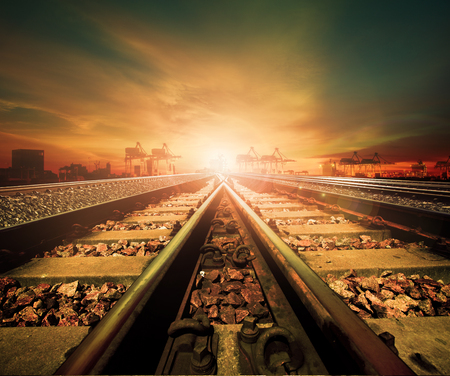 railway: junction of railways track in trains station agains beautiful light of sun set sky use for land transport and logistic industry background ,backdrop,copy space theme