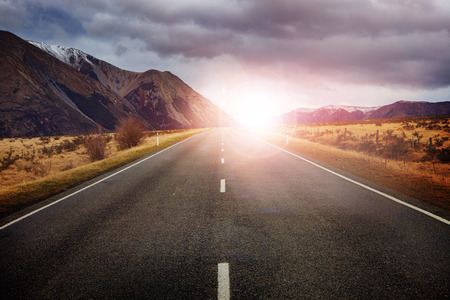 angle: beautiful sun rising sky with asphalt highways road against snow mountain arthurs pass scenery background in new zealand Stock Photo