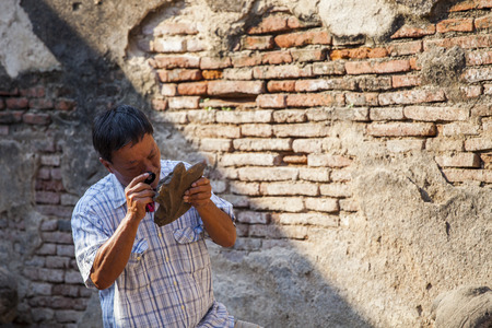 archaeologist: old Archaeologist using magnifying lens watching on ancient old in working site