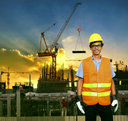 worker man: asian construction site worker smiling face and building construction site background