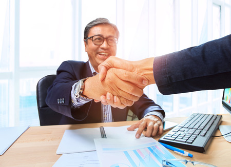 smiling businessman: two business man shaking hand with happiness emotion after agreement in working solution ,shot on office working table