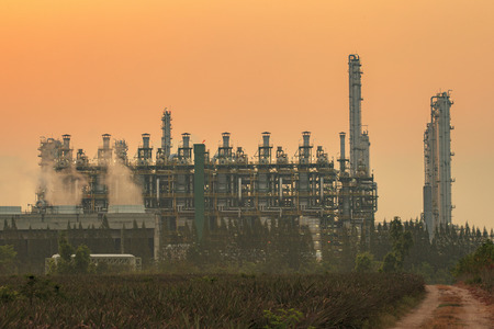 industrial industry: exterior tube of petrochemical plant and oil refinery for produce industrial material in heavy petroleum industry estate against beautiful sun light sky