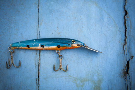 old fishing lure on blue wood background Banco de Imagens