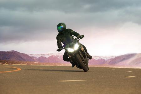 Joven montado en motocicleta grande en la carretera de asfalto, uso para la gente que viaja de ocio y estilo de vida de aventura Foto de archivo - 60798833