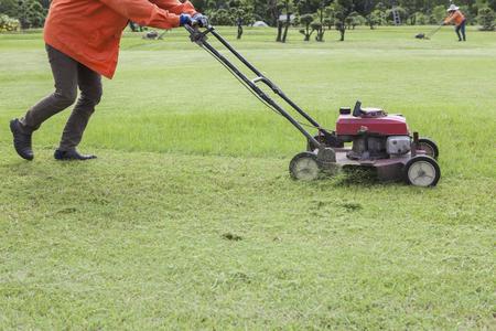 obrero trabajando: trabajador y de la podadora que trabajan en el campo de hierba verde