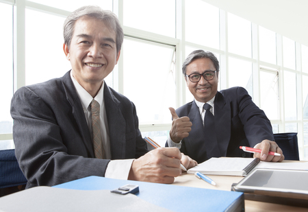 two of asian business man toothy smiling face ,relaxing in office life 스톡 콘텐츠