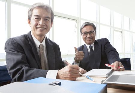 2 つのアジア ビジネスの男はこぼれるような笑顔、オフィスの生活でリラックス