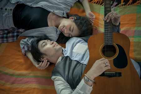 younger: couples of asian younger man and woman playing guitar with relaxing and happiness emotion