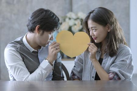 アジア人男性と心臓の形状の紙を保持している女性のカップル カット幸福感情の peple の愛の概念