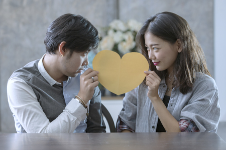 couples of asian man and woman holding heart shape paper cut with happiness emotion ,peple love conceptual 스톡 콘텐츠
