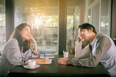 アジアの若い男とコーヒー ショップ幸福感でホット コーヒーを飲むとリラックスできる女性のカップル