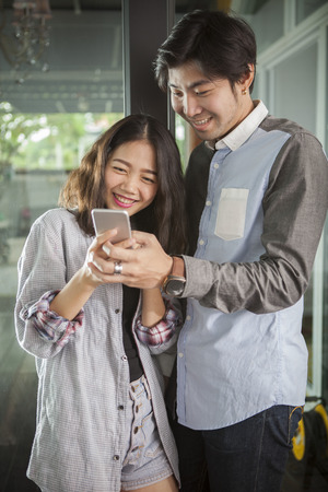 chatting: asian younger man and woman watching on smart phone with happy face,internet and social media concept