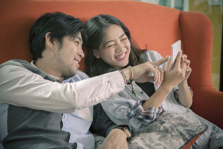 asian younger man and woman watching on smart phone with happy face,internet and social media connecting concept