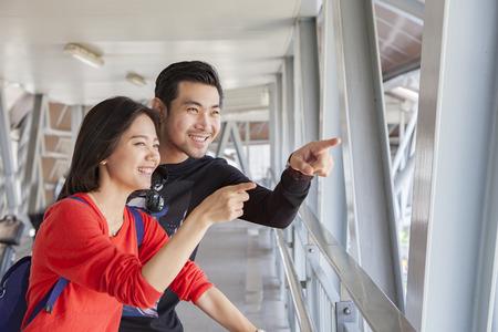 Parejas de hombre asiático joven que viaja y una mujer mirando y señalando a los turistas el lugar de llegada sonriendo emoción felicidad cara Foto de archivo - 61868856