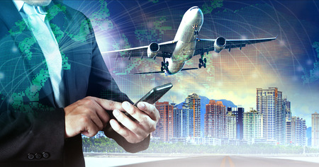flight: business man touching on smart phone and air plane flying mid air against city building and world map network Stock Photo