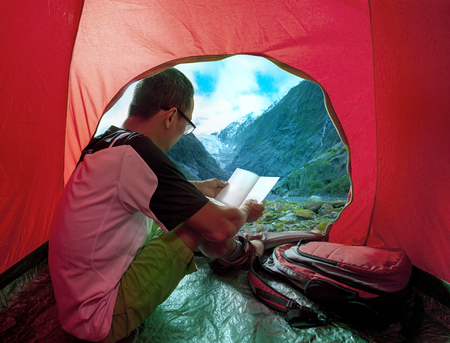 camping man reading a traveling guild book in camp tent beautiful mountain scenic