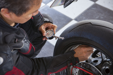 air pressure: biker checking air pressure in rear wheel of big motorcycle Stock Photo