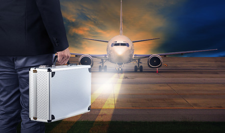 runways: business man with metal strong luggage standing in airport runways and air plane preparing to departure