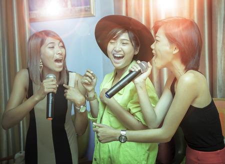 Aziatische jonge vrouw zingen karaoke met ontspannen en emotie geluk