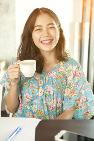 hot asian: asian woman smiling face happiness emotion and hot beverage cup in hand relaxing at home
