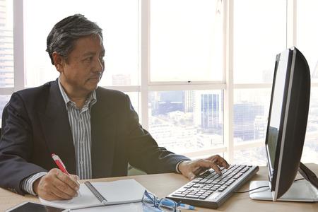 early 60s: senior asain business man writing and working on pc computor