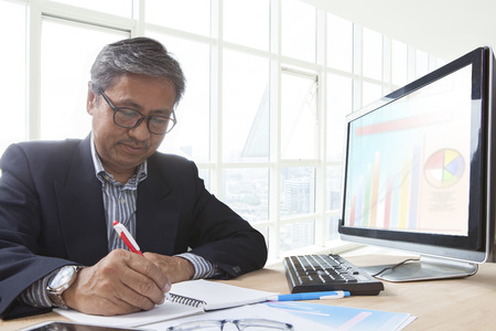 office life: asian senior business man working on computer table for office life theme Stock Photo